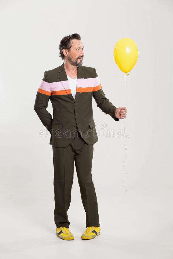 Happy man with yellow balloon. Cute brunette male in funny suit. Holding yellow balloon royalty free stock images