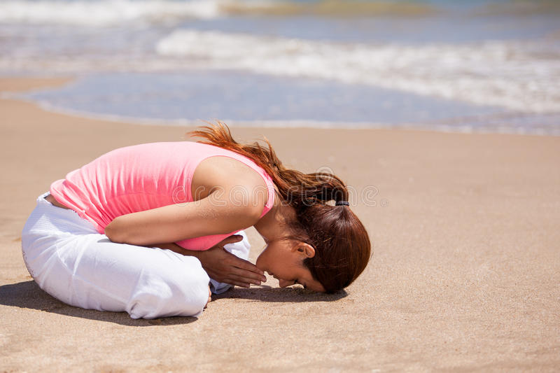 Cute brunette meditating outdoors. Pretty Hispanic woman meditating and doing some yoga at the beach stock photography