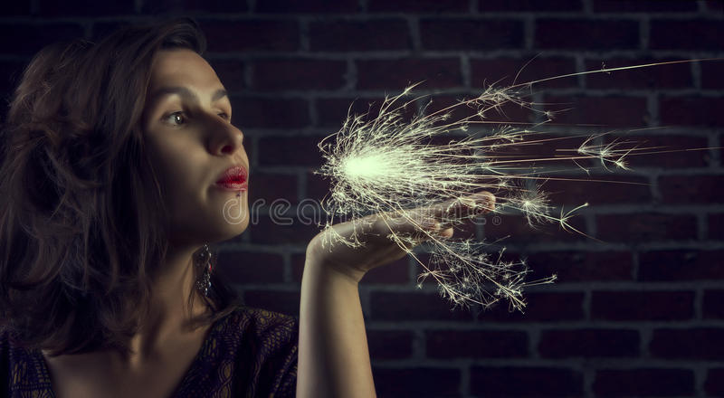 Cute brunette woman blowing bengal light stock photos