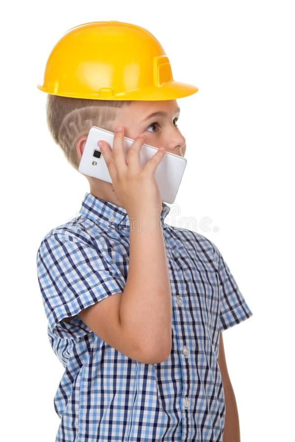 Cute builder boy speaks by phone, wearing yellow protectie helmet and blue checkered shirt. White background. royalty free stock photos