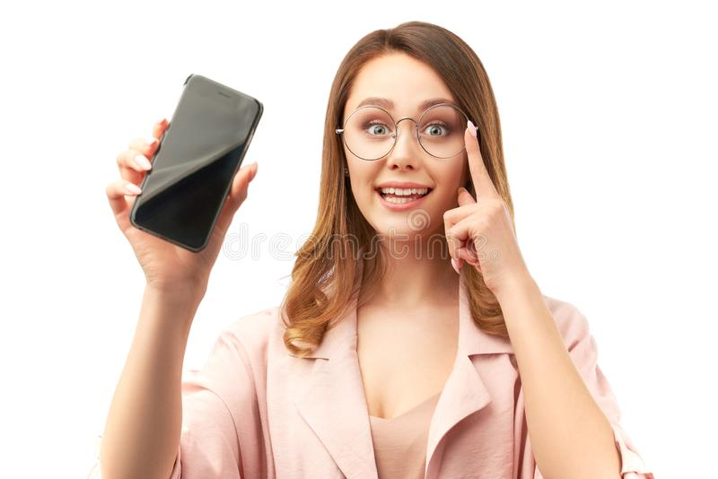 A cute business woman holding a phone in her hand and showing a blank smartphone screen. royalty free stock photography