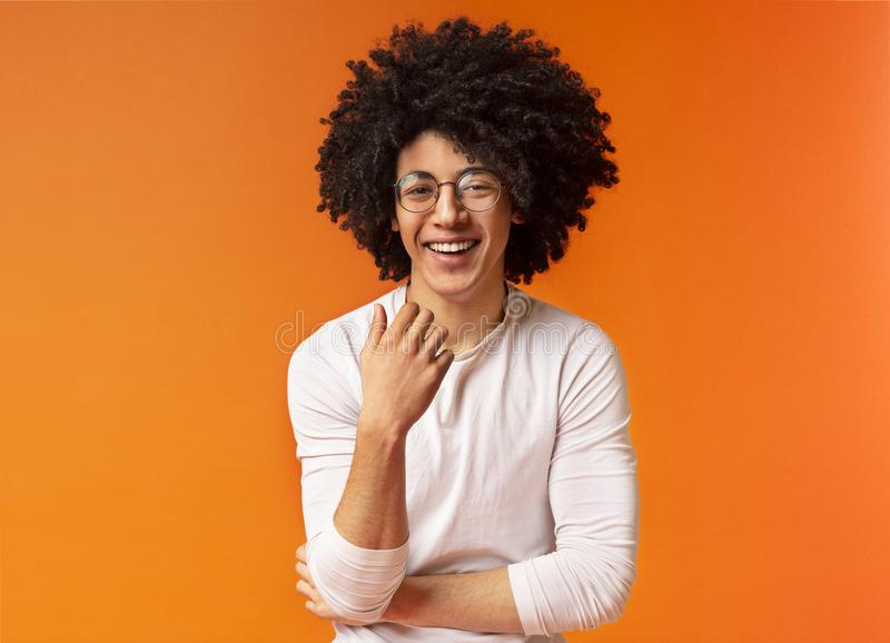 Cute carefree black curly guy laughing on orange background stock images