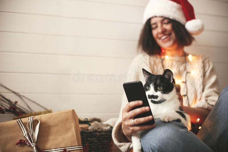 Cute cat looking at phone screen with funny emotions and sitting on happy girl legs in christmas lights. Young hipster woman in. Santa hat hugging kitty and royalty free stock image