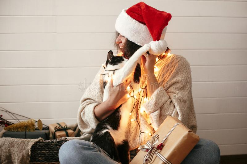 Cute cat playing with santa hat on stylish happy girl in festive christmas lights on background of modern presents. Young funny. Woman in cozy sweater playing stock image