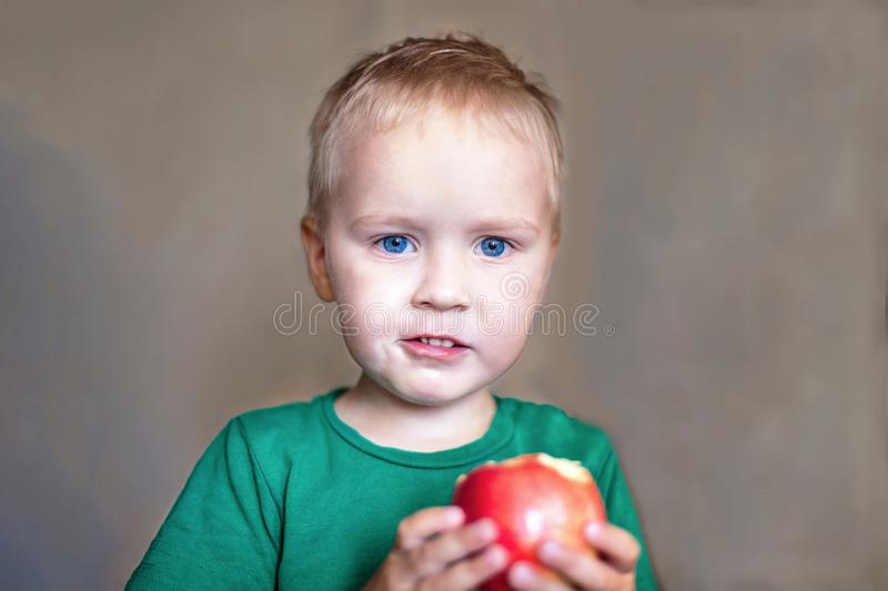 Cute caucasian baby boy with blue eyes and blonde hair in green t-short eats red apple, holding it on the hands stock image