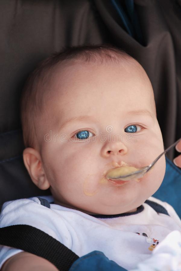 Cute caucasian baby boy fed from small spoon in baby chair. Close up portrait of pretty baby with bright blue eyes. stock photos