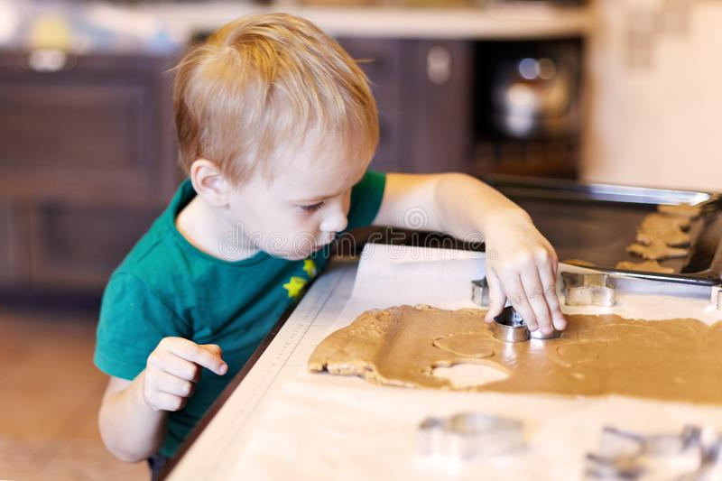 Cute caucasian baby boy helps in kitchen, making homemade coockies. Casual lifestyle in home interior, pretty child, holiday conce royalty free stock images