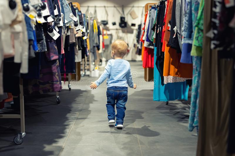 Cute caucasian blond toddler boy walking alone at clothes retail store between rack with hangers. Baby discovers adult shopping. World. Baby get lost at big stock photo