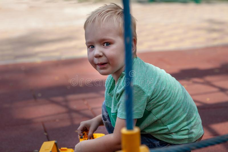 Cute caucasian blonde baby boy with blue eyes sits on the cover of children playground with a toy, yellow excavator. Funny look, a stock photo