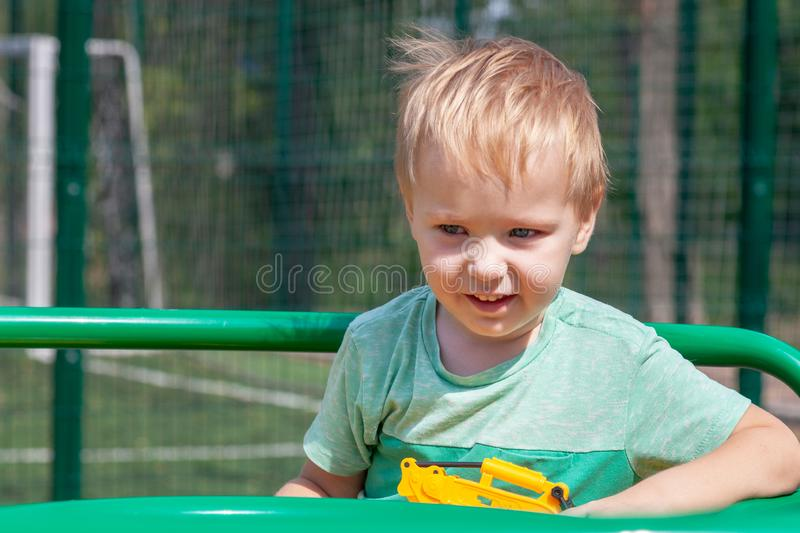 Cute caucasian blonde baby boy plays on the playground, smiling, with yellow toy in the hand. The emotion of happiness, fun, joy. Outdoors, copy space, green stock images