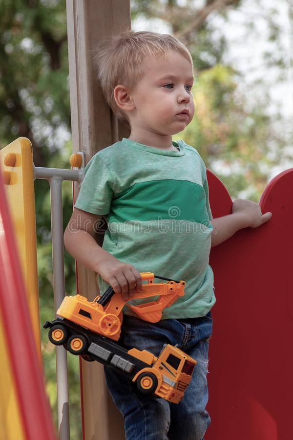 Cute caucasian blonde baby boy stands with a toy yellow excavator on the children playground. Alone, serious and humile expressi royalty free stock photography