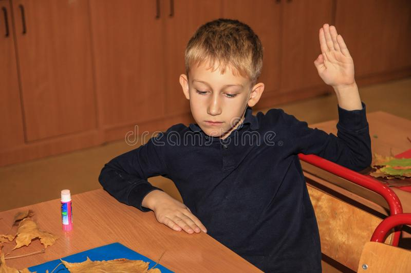 Cute Caucasian boy, elementary school student sitting at table with the with handcraft. He raised his hand. royalty free stock photos