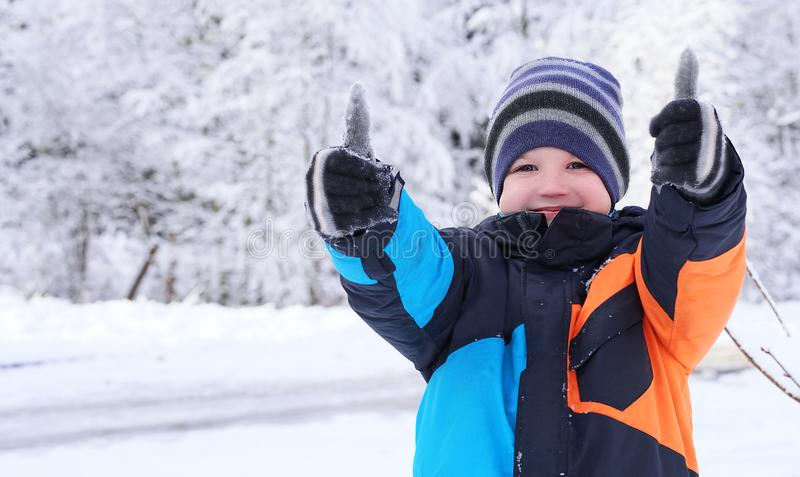 Cute Caucasian boy giving thumbs up, playing and laughing on snowy winter walk in nature. Frost winter season. Cute Caucasian boy giving thumbs up, playing and stock image