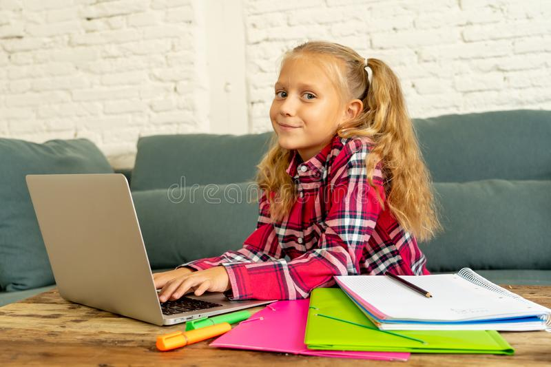 Cute caucasian cheerful elementary student feeling happy while doing homework and studying on her laptop in living room at home in. New technology school stock photo