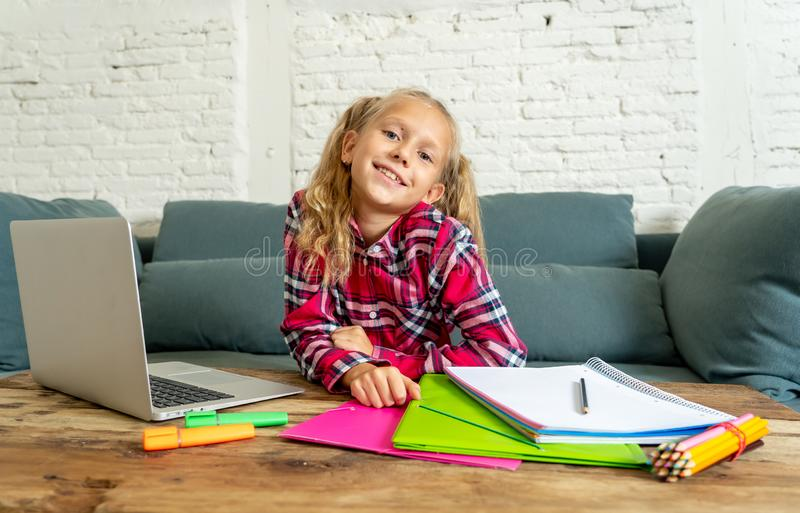 Cute caucasian cheerful elementary student feeling happy while doing homework and studying on her laptop in living room at home in royalty free stock photos