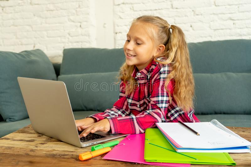 Cute caucasian cheerful elementary student feeling happy while doing homework and studying on her laptop in living room at home in. New technology school stock photography