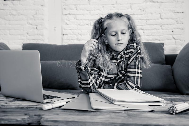Cute caucasian cheerful elementary student feeling happy while doing homework and studying on her laptop in living room at home in stock photography