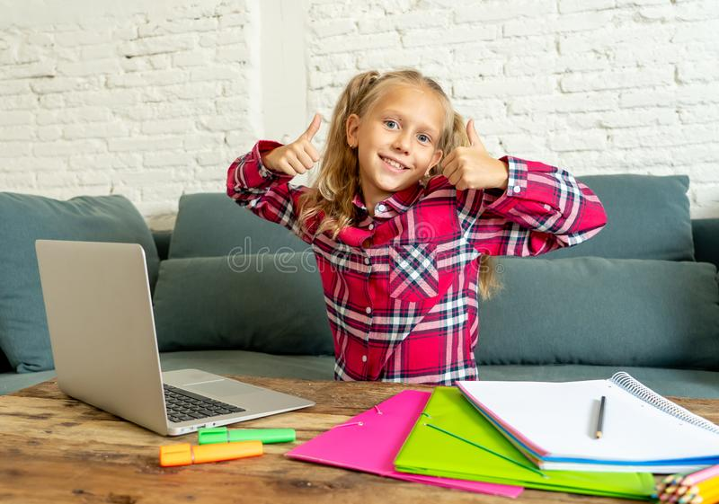 Cute caucasian cheerful elementary student feeling happy while doing homework and studying on her laptop in living room at home in royalty free stock photography
