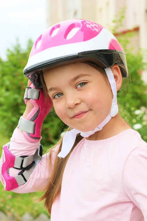 A cute Caucasian child wearing a helmet and roller guard stock images
