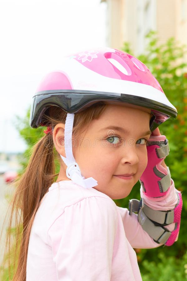 A cute Caucasian child wearing a helmet and roller guard stock photos