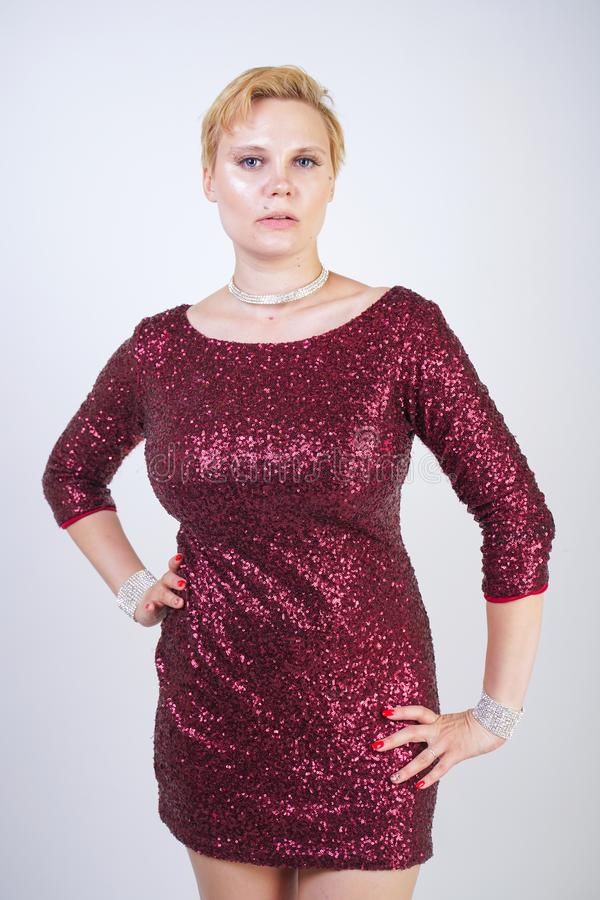 Free Cute Caucasian Curvy Girl With Short Blonde Hair And Plus Size Body Wearing Beautiful Elegant Cherry Color Dress With Sequins And Stock Photo - 150449200