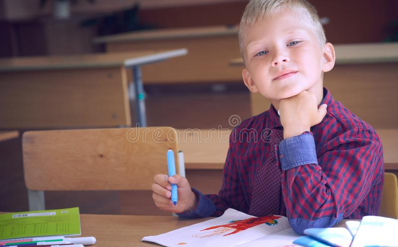 Cute Caucasian doing homework, coloring pages, writing and painting with felt pens. Children paint. Felt pens and paper. Cute Caucasian doing homework, coloring royalty free stock photos