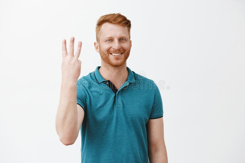 Cute caucasian friendly redhead man ordering three shots from bartender, smiling broadly showing number third and stock photo