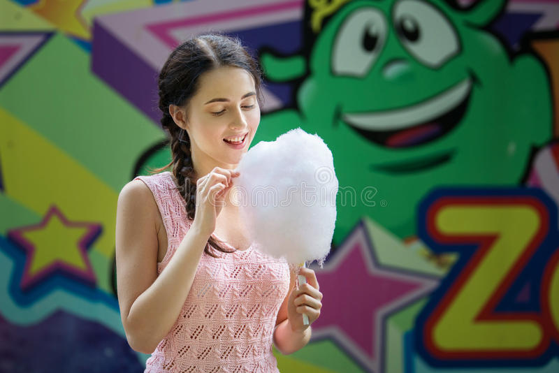 Cute caucasian girl in amusement park is eating pink candyfloss. Portrait of happy attractive young woman with cotton candy. royalty free stock photos
