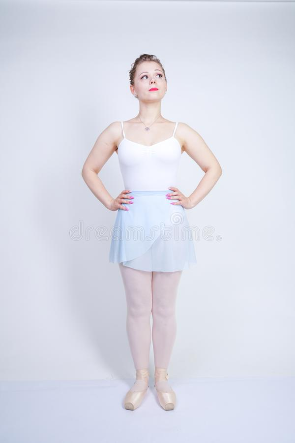 Cute caucasian girl in ballet clothes learning to be a ballerina on a white background in the Studio. plus size young woman dreams stock photos