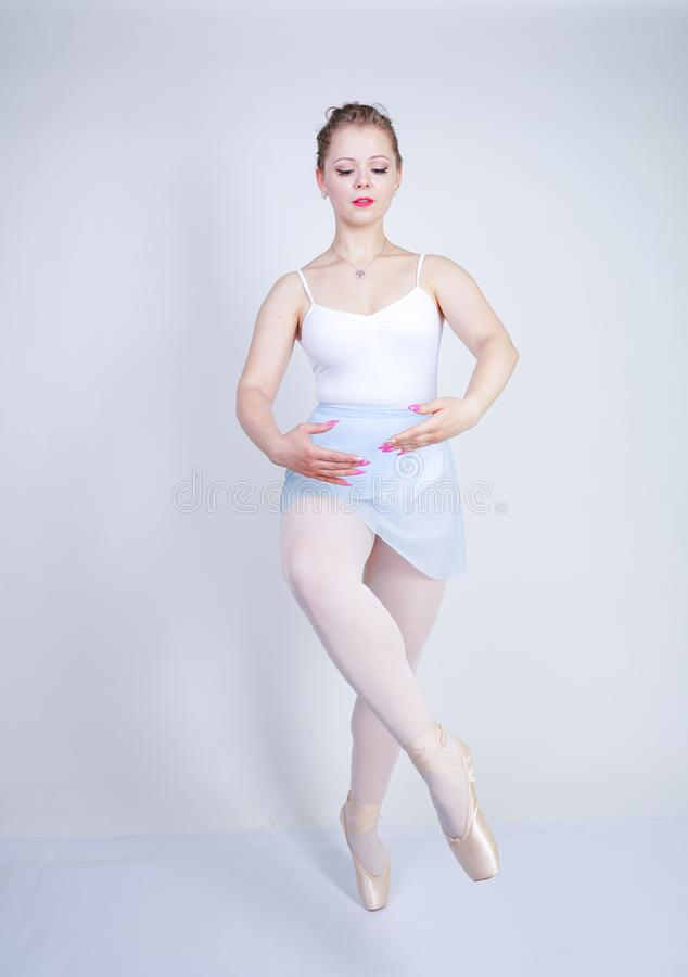Cute caucasian girl in ballet clothes learning to be a ballerina on a white background in the Studio. plus size young woman dreams stock photo