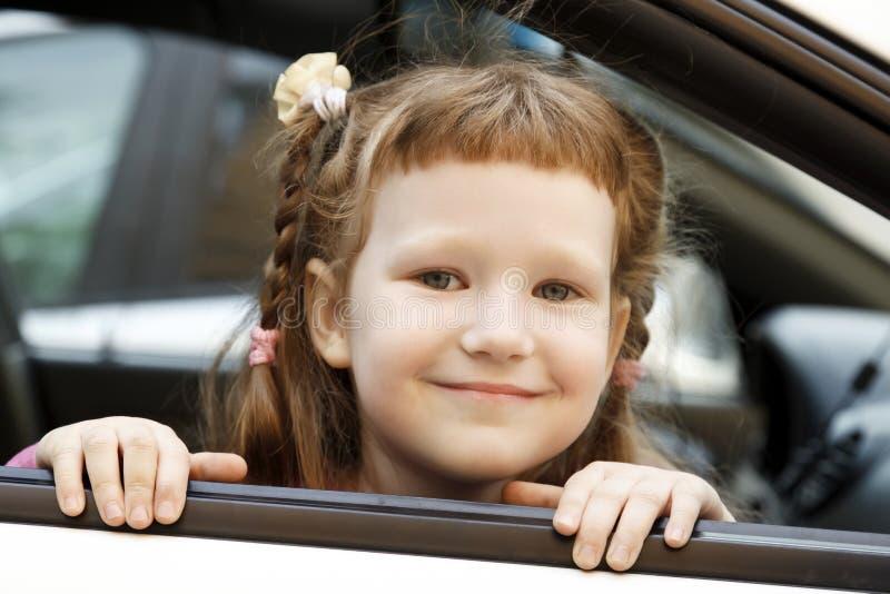 Cute caucasian girl in a car stock images