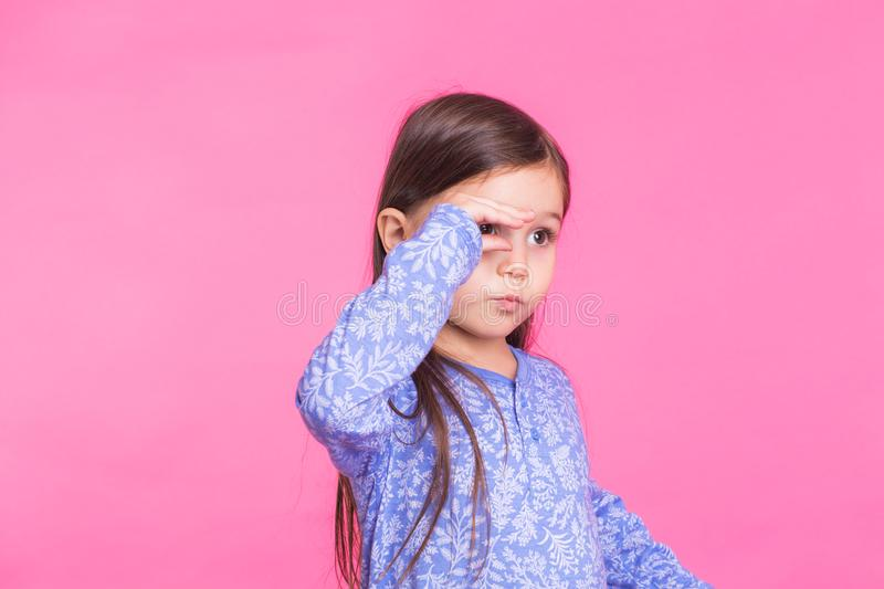 Cute caucasian girl fooling around on pink background stock photo