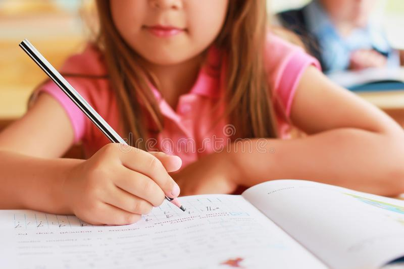 A sweet Caucasian child in school at a desk writes in a notebook royalty free stock image