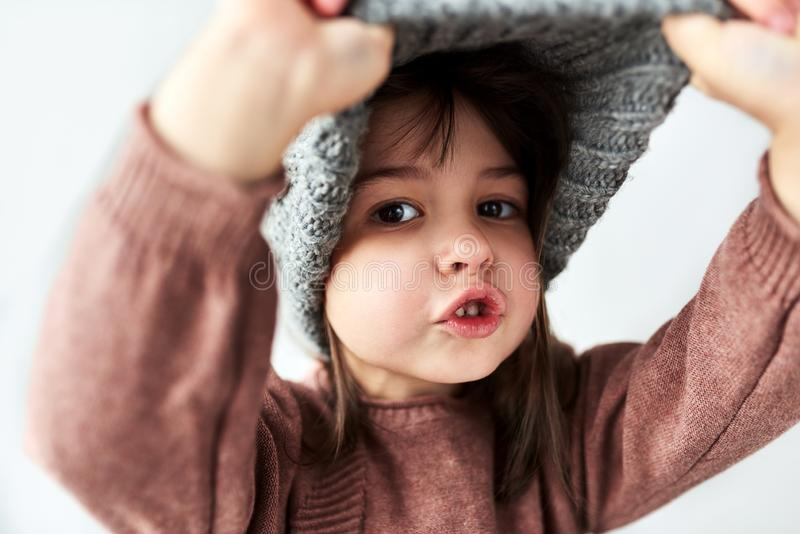 Cute Caucasian little girl playing peek-a-boo with the winter warm gray hat, wearing sweater isolated on a white studio background royalty free stock images