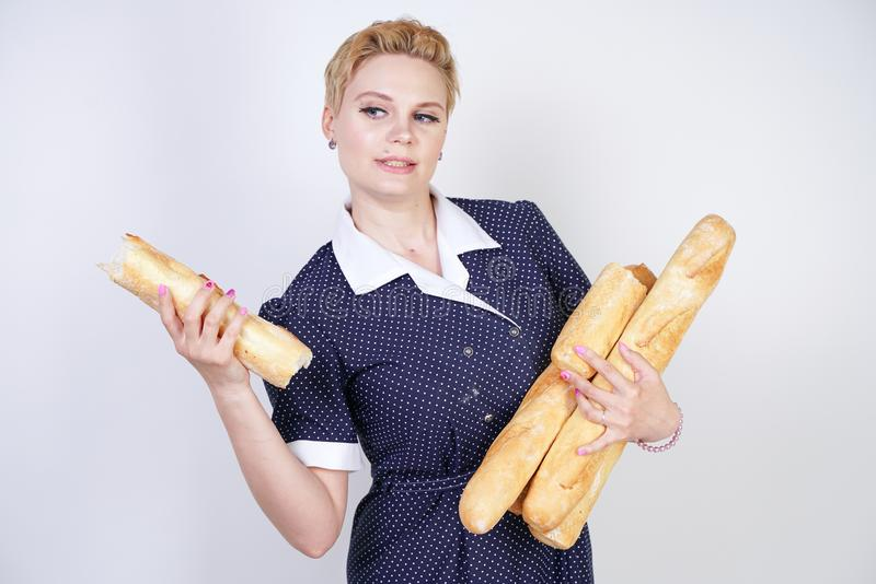 Cute caucasian pinup girl wearing vintage polka dot dress and holding baguettes on a white background in the Studio. Isolated stock photography