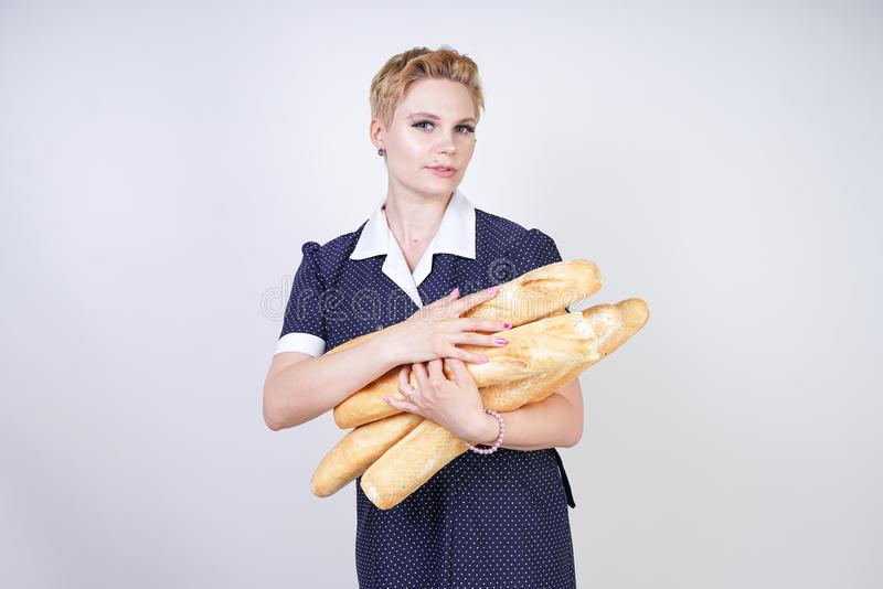 Cute caucasian pinup girl wearing vintage polka dot dress and holding baguettes on a white background in the Studio. Isolated stock photos