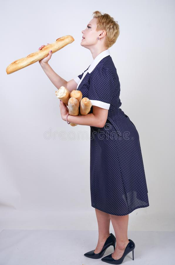 Cute caucasian pinup girl wearing vintage polka dot dress and holding baguettes on a white background in the Studio. Isolated royalty free stock photos