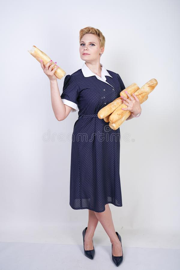 Cute caucasian pinup girl wearing vintage polka dot dress and holding baguettes on a white background in the Studio. Isolated stock photo