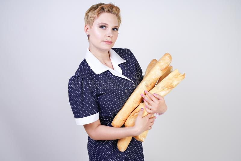 Cute caucasian pinup girl wearing vintage polka dot dress and holding baguettes on a white background in the Studio. Isolated royalty free stock photo