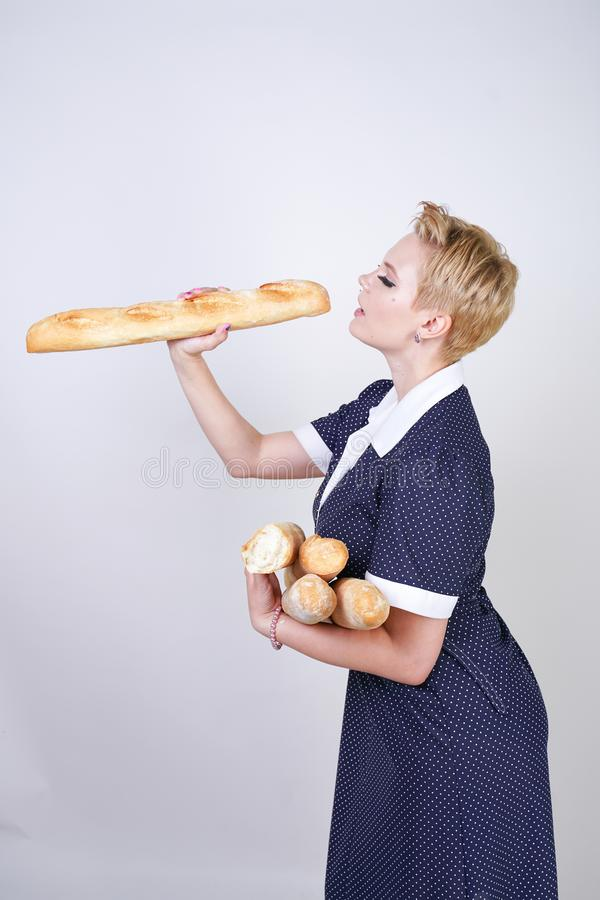 Cute caucasian pinup girl wearing vintage polka dot dress and holding baguettes on a white background in the Studio. Isolated royalty free stock photography