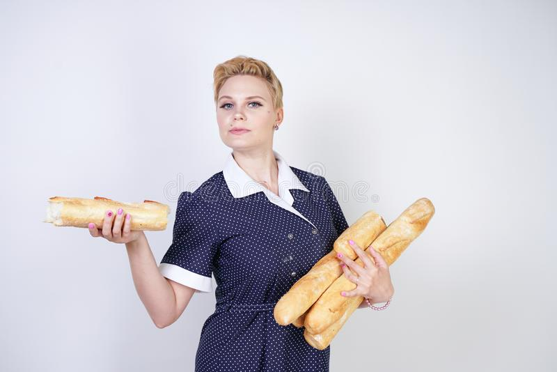 Cute caucasian pinup girl wearing vintage polka dot dress and holding baguettes on a white background in the Studio. Isolated stock images