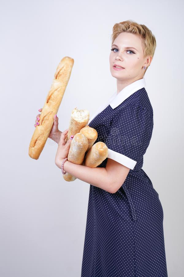 Cute caucasian pinup girl wearing vintage polka dot dress and holding baguettes on a white background in the Studio. Isolated royalty free stock images