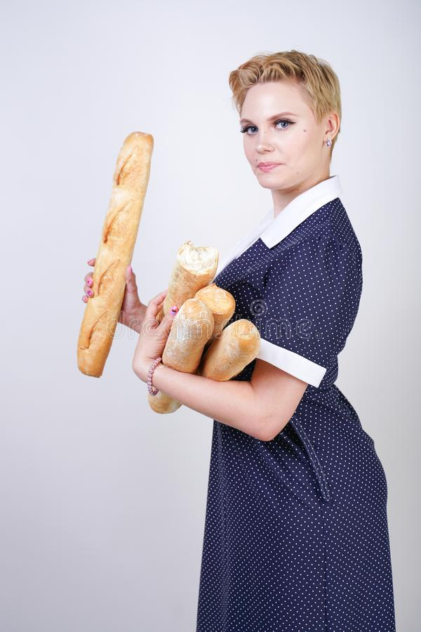 Cute caucasian pinup girl wearing vintage polka dot dress and holding baguettes on a white background in the Studio. Isolated stock image