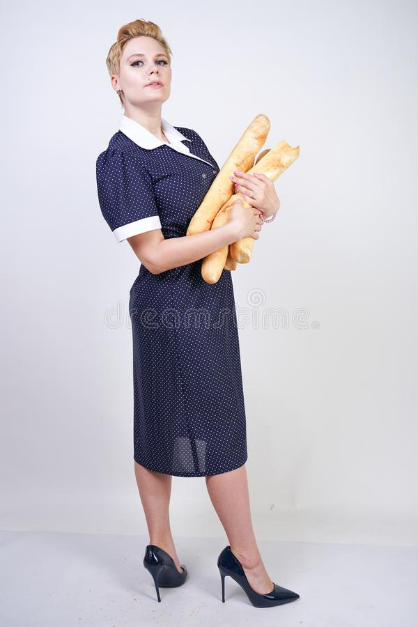 Cute caucasian pinup girl wearing vintage polka dot dress and holding baguettes on a white background in the Studio. Isolated royalty free stock image