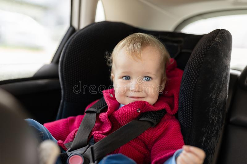 Cute caucasian toodler boy sitting in child safety seat in car during road trip. Adorable baby smiling and enjoying trip in stock photography
