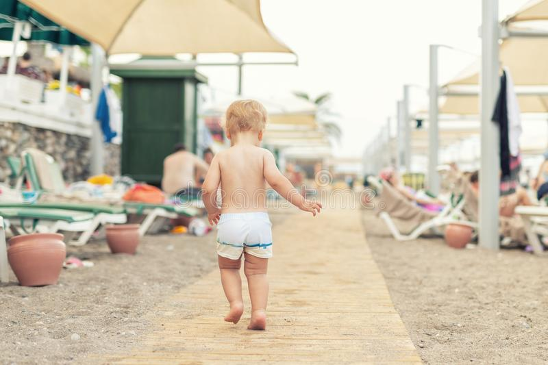 Cute caucasian toodler boy walking alone on sandy beach between chaise-lounge. Adorable happy child having fun playing at seaside. Shore during vacation trip stock photo