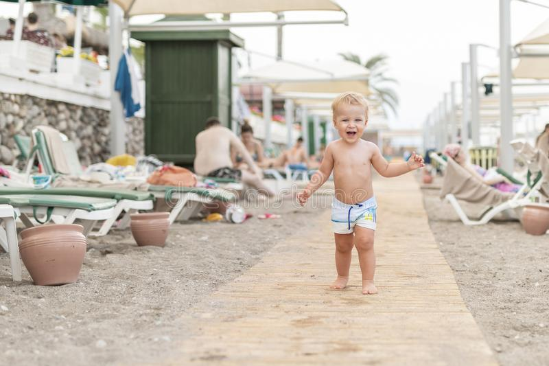Cute caucasian toodler boy walking alone on sandy beach between chaise-lounge. Adorable happy child having fun playing at seaside. Shore during vacation trip royalty free stock image