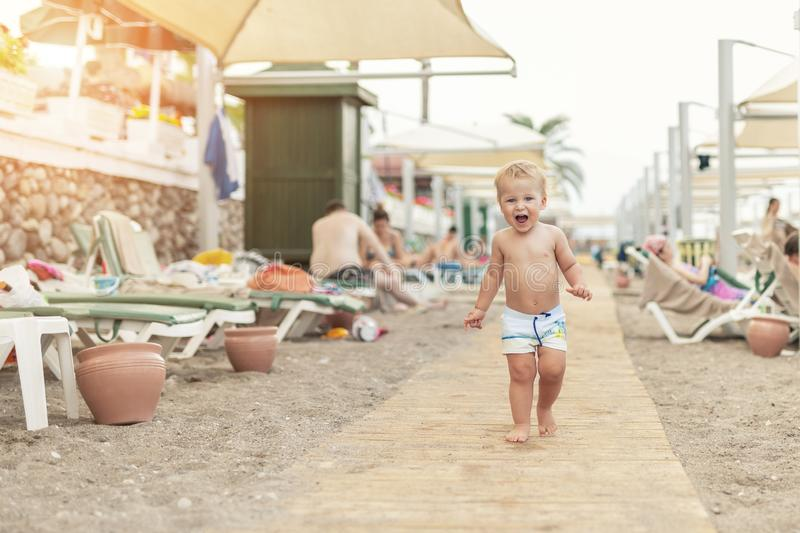Cute caucasian toodler boy walking alone on sandy beach between chaise-lounge. Adorable happy child having fun playing at seaside. Shore during vacation trip stock image