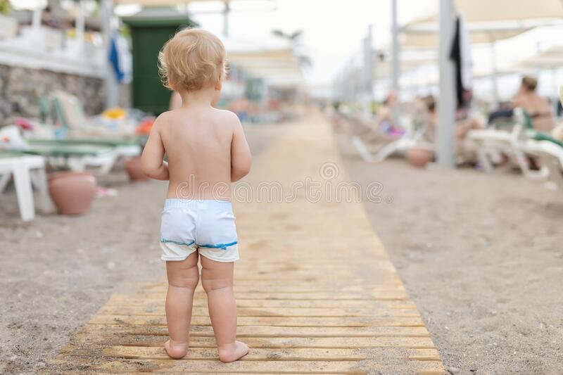 Cute caucasian toodler boy walking alone on sandy beach between chaise-lounge. Adorable happy child having fun playing stock images