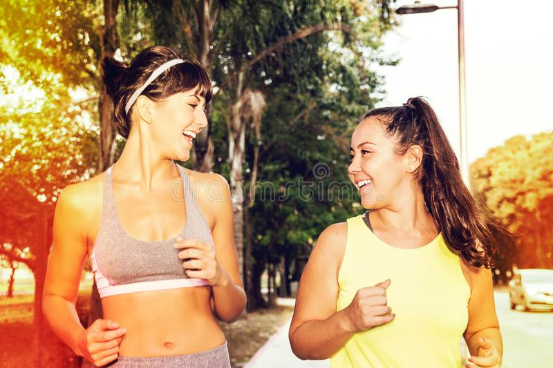 Cute caucasian woman and pretty asian girl enjoying a run outside. Friendship and sports concept. royalty free stock photography